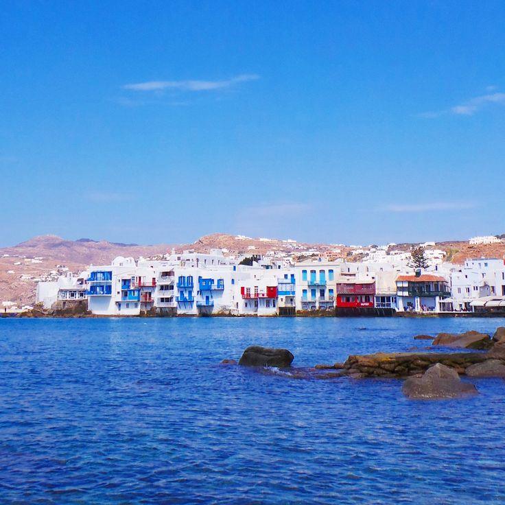 A row of beautiful old greek buildings line the entrance to Mykonos port.. #mykonos #holiday #architecture #port #coast #sea #mykonoslife #visitgreecegr #contrast #travel #mediterranean #colour