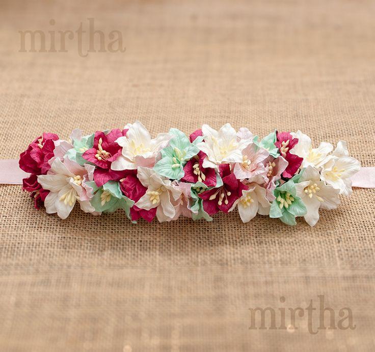 Cinturón de flores de papel sobre lazo blanco compuesto por una combinación de lirios en color blanco, turquesa, rosa y buganvilla.