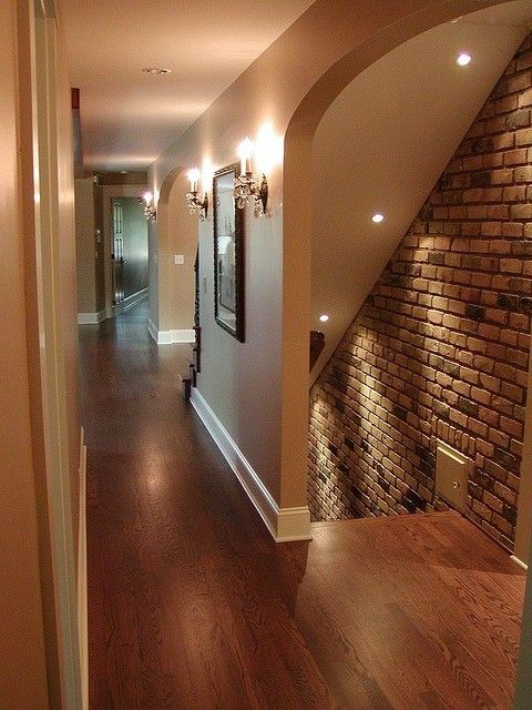 Basement entrance. Love the lighting and brick wall and how inviting it is with no door! And the sconces!