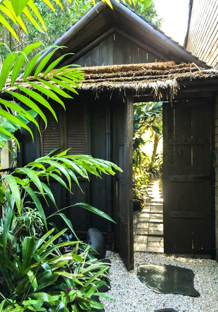 Garden shed, access to backyard, and tropical set-dressing all wrapped up in one...