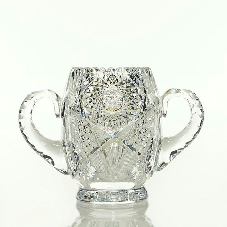 """Unique cut glass trophy-like vase with twin double notched """"ear"""" handles and a 16 point hobstar on the disc base. The body cut in hobstars, cane and fans with a sawtooth edge. Measures 6 1/2 inches by 9 1/4 inches across the handles. Unusual shape. Minor 1/8 inch pattern chip. Heavy 5 pound blank."""
