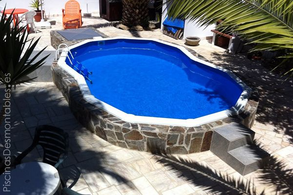Piscina Gre Serie Varadero con forma de 8. Medidas: 550 x 340 x 120 cm. La piscina está semienterrada (20 cm) y tiene una escalera de dos peldaños anchos. Esta piscina no tiene contrafuertes laterales (están ocultos por debajo de la piscina) y se ha construido un muro de piedra que bordea toda la piscina. El aspecto final es espectacular. Foto: Carlos Veiga.