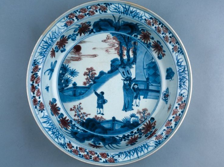 Porcelain dish with rounded cavetto and flattened rim curving upward at the edge, decorated in underglaze cobalt blue and copper red. A scene of a man with two servant boys admiring the moon on a terrace beside a pavilion; one servant carries a large fan and the other a qin in a silk bag. Inscription on base. Qing dynasty Kangxi period.