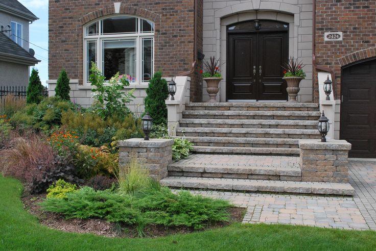 Aménagement d'un façade de maison avec des dalles de pavé Permacon Mondrian et muret Celtik. Grand espace de plantation avec vivaces, graminées et arbustes. Lampes et pots de fleurs.