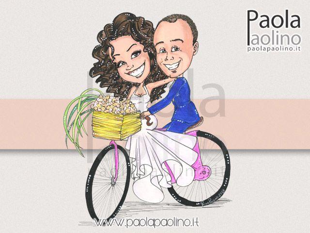 #Caricatura di due #sposi su #bicicletta che convolano a #nozze, con un bel #cestino colmo di #fiori.