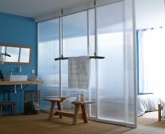 Une cloison en plaque polycarbonate sépare chambre et salle de bains tout en laissant passer la lumière.