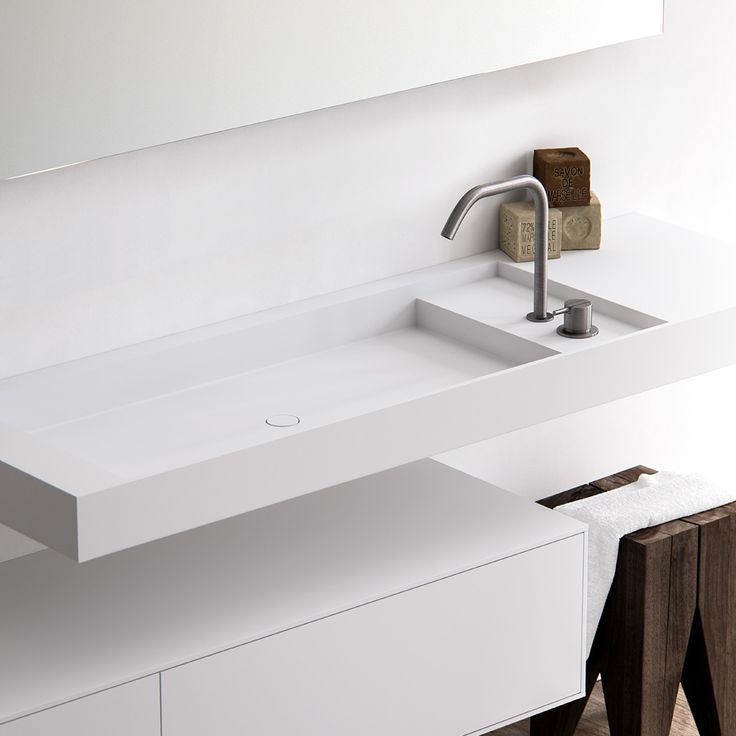 Level, named after its difference in levels with a raised surface. Ideal for a basin mounted tap and handsoap. Practical and beautiful, it has the option of positioning the plateau at the sides or back of the basin - a true design classic. Completely made to measure washbasin out of HI-MACS (solid surface). Featured: Wall mounted Level washbasin in Alpine white HI-MACS with a matching HI-MACS wall mounted cabinet. Platform positioned at the side. bathsbyclay.com