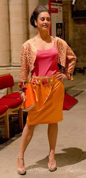 Bright orange skirt with swag attachment on skirt. Contrast embroidered animal print jacket