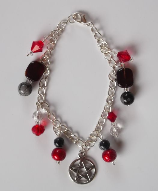 Wicca Charm Bracelet:  A silver chain sets off the striking red & black beads of this attractive wicca themed bracelet. Metal pentagram charm. Size 190mm/7 1/2""