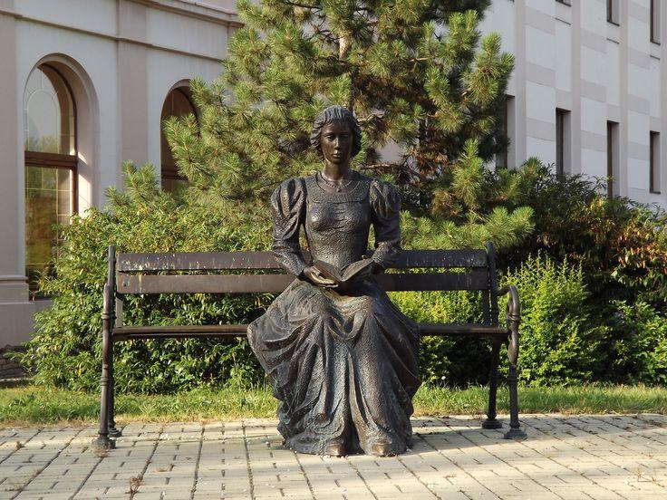 Józsa Lajos: Az olvasó nő szobra Szentes, a Városi Könyvtár előtti park