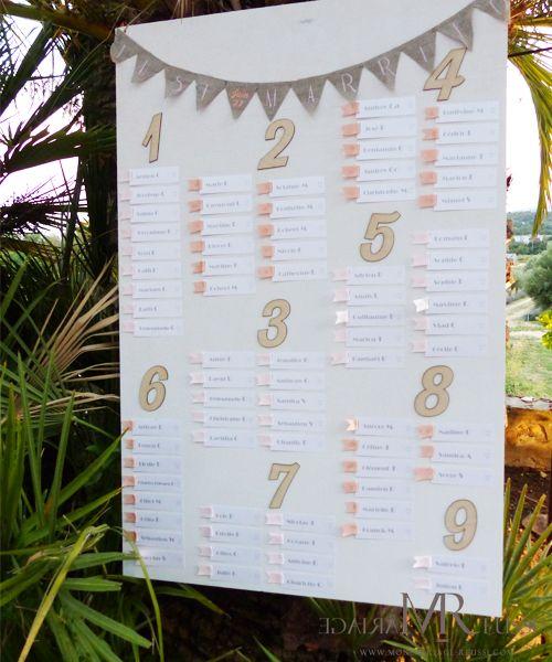 Plan de table bohème chic, fanions en lin, chiffres découpés au laser dans du bois, étiquettes imprimées sur papier irisé blanc et ruban de satin rose et pêche