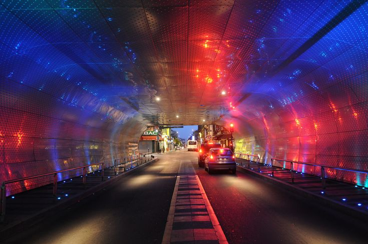 Designer:  Exit Paysagistes Associés  Project: Sub-face of The Railroad Bridge  Location: Sartrouville, France.    he project creates a luminous volume you can see from the Avenue de la République in the daytime and at night. The tunnel's envelope made of stamped stainless sheet steel adopts the light variations of the city and establishes a lightning continuity from the street to the tunnel.     http://exitpaysagistes.com/en/2011/01/pon/