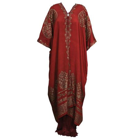 Mariano Fortuny Burgundy Stencilled Crepe Coat. Italy.  Pattern Creatian Tree. This ankle length silk crepe wrap, based on antique ethnic caftan styles, is cut square with openings for the arms. A stenciled Fortuny garment has minimal cuts so that the garment can serve as a canvas for the art work. The hand stenciling is done with real gold metallic pigments aged to a mellow, burnished color. Fortuny built his stenciled pieces layer upon layer, until he achieved the effect of an ancient…