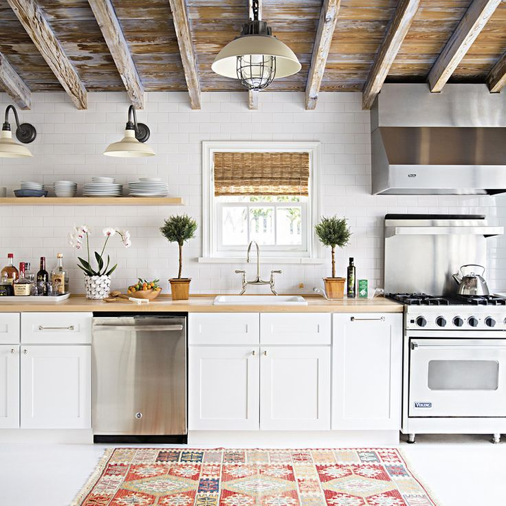 A two-bedroom 1930s bungalow gets a 60-day lightning round of renovations that involved gutting this kitchen, improving the floor plan, and so much more – a crisp blue-and-white palette with touches of driftwood and rattan