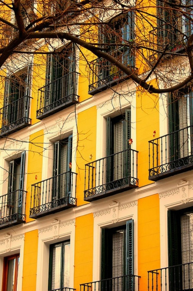 yellow building with iron window railings