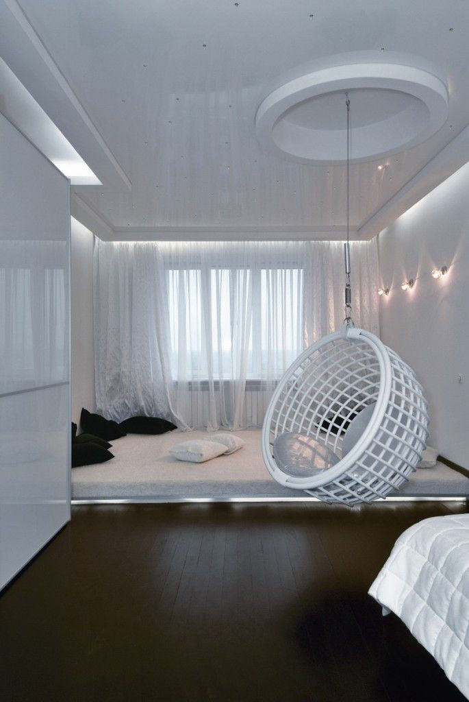 Futuristic small apartment interior design with white hanging pod chair and white color theme use