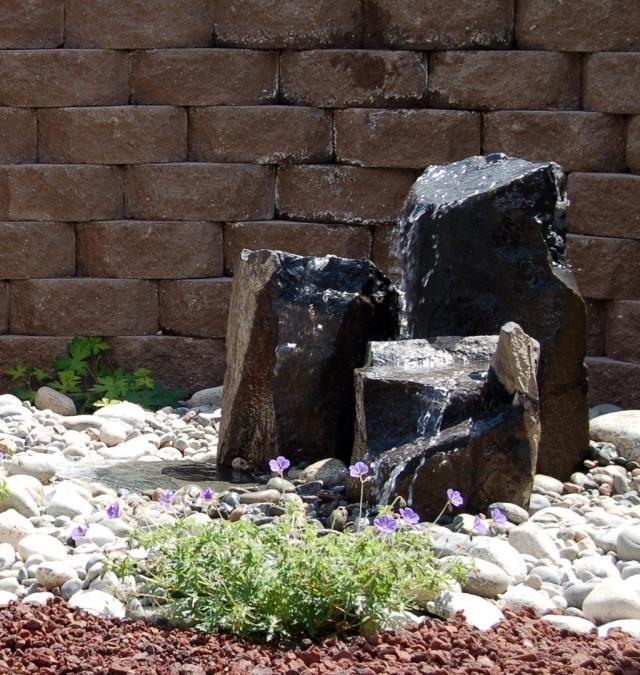 brunnen pumpe naturstein schwarz weißer kies garten wasserspiel