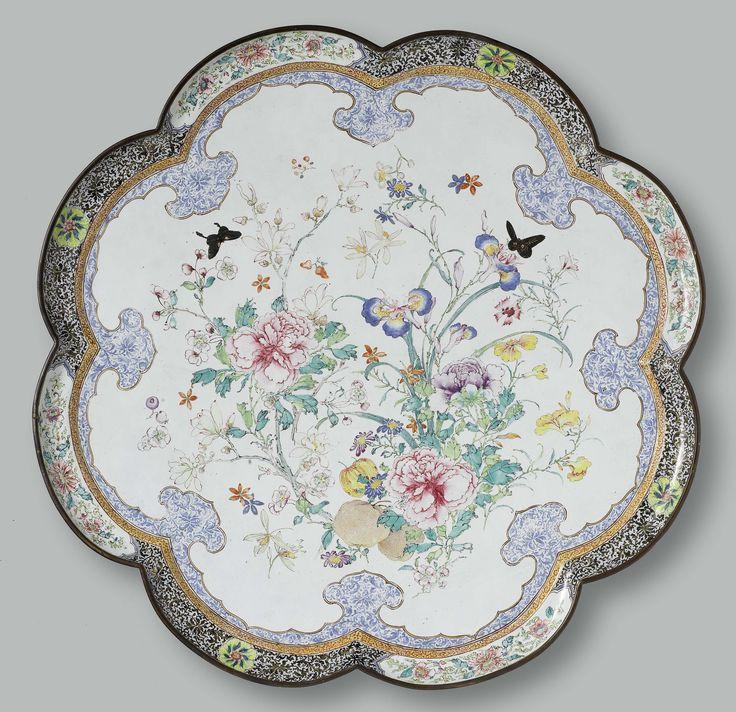 Anonymous | Schotel, achtlobbig, beschilderd met bloemtakken, Anonymous, c. 1730 | Achtlobbige schotel, in het plat beschilderd met grote bloemtakken die grotendeels linksonder zijn samengenomen tot een boeket. Daartussen srtooibloemen en twee vlinders. Bij de bloemen vallen vooral de pioenen, irissen, magmoliatakken en ugly-vruchten op. De voorstelling wordt omgeven dooe een lambrquin-band, opgevuld met blauwe ranken. In de rand een brokaatmotief met afwisselend een veld met pioenrozen en…