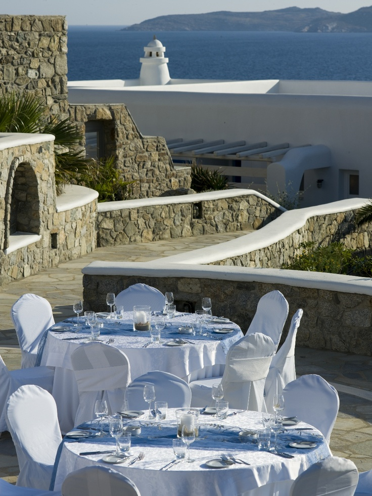 Gala setup detail with Mykonian Chimney on the background, at outdoor amphitheater of Mykonos Grand Beachfront Hotel