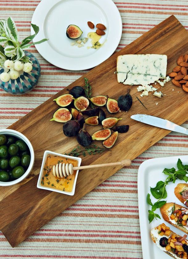 pretty appetizer board with olives, figs, honey, cheese, almonds, and crostini