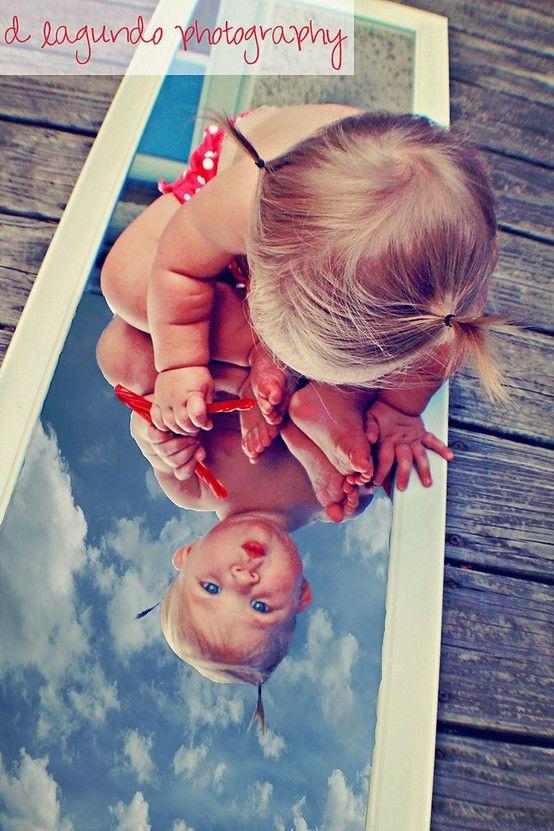 menininha olhando sua imagem e o céu refletido no espelho :)