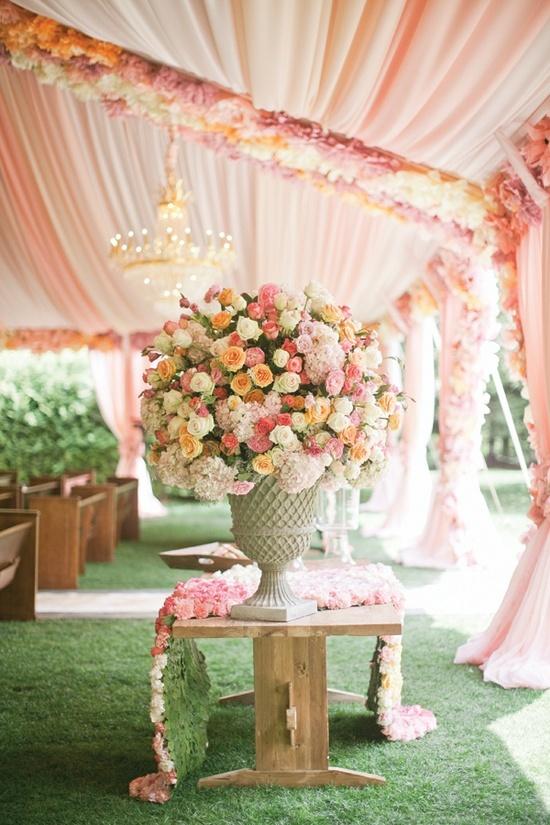 Ideia para um casamento ao ar livre com tenda usando tecido coordenado com as cores das flores.