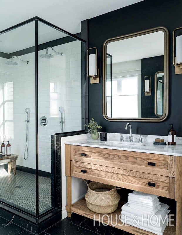 In the newly created principal bathroom, black walls, coordinating marble-look floor tiles and a dramatic shower enclosure are edgy and striking. A wooden vanity softens the high-contrast color scheme. | Photographer:André Rider | Designer: Mélanie Cherrier, Blanc Marine Living