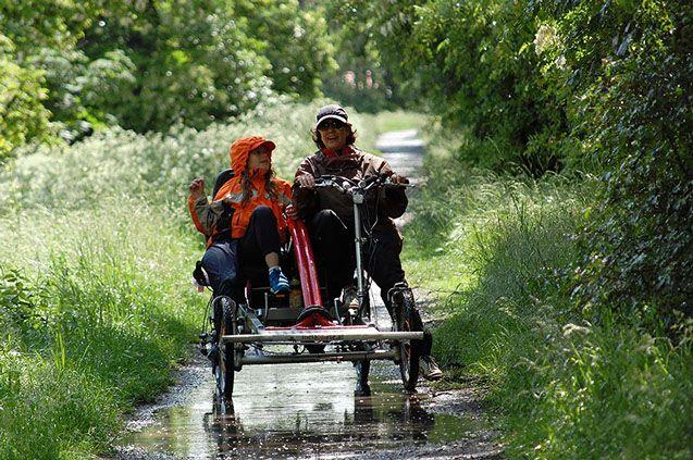 Radwandern mit Vierrad Tandem Fahrrad metallhase mit der richtigen Bekleidung im Regen.