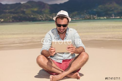 smiling man reading on  tablet  while sitting down the beach