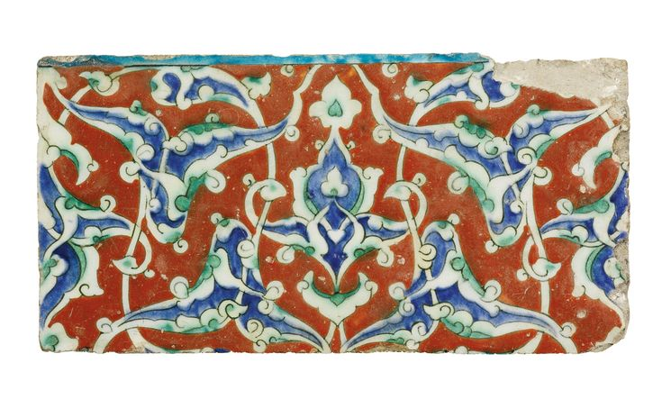 AN IZNIK POLYCHROME POTTERY TILE, TURKEY, CIRCA 1580 of rectangular form, decorated in underglaze cobalt blue and viridian green between a relief red ground, with a turquoise band to top, the design featuring interlacing split-palmettes 24.7 by 12.5cm.