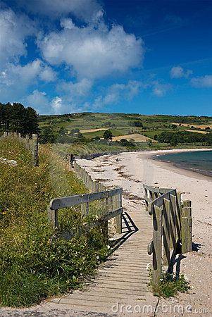 Wooden pathway leads down to the sandy beach at Cushendun, County Antrim, Northern Ireland, where a solitary figure sits in the sun.