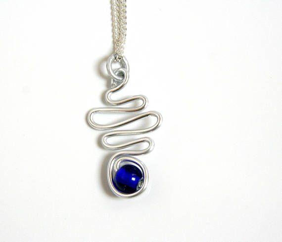 Un collier simple et classe avec un pendentif orné dune jolie perle bleu profond. Se marie parfaitement avec de simples jeans foncés par exemple, mais aussi avec une robe bleu marine par exemple. ♠ Dimensions Pendentif 4,5 cm de haut pour environ 2,5 cm de large Perle bleu profond de 0,8 mm de diamètre Chaînette fine de 48 cm de long en métal argenté avec fermeture mousqueton argentée (précisez si vous souhaitez une autre longueur de chaînette).    ☼ R E T R O U V E Z - M O I Sur Instagram…