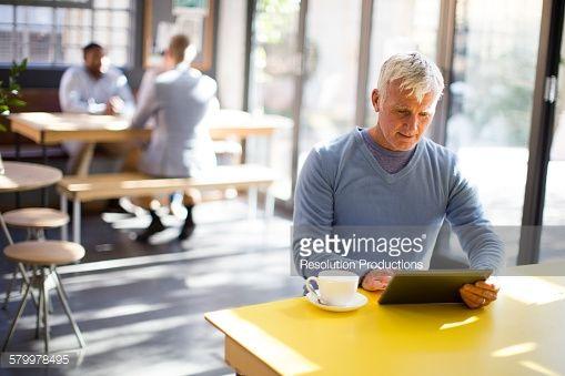 Stock Photo : Older man using digital tablet in cafe