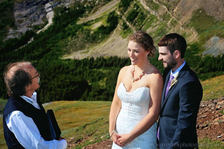 Bride, groom and officiant on mountain side during wedding ceremony in Canmore Alberta. Canmore Alberta weddings.