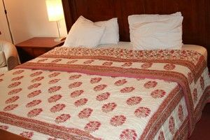 The image showing super king size quilted bedspreads with beautiful prints in red colour with off white base.