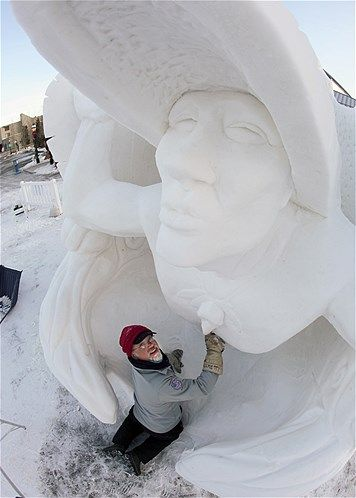 Image: Pete Lucchetti builds his snow sculpture named ''Raven Myth'' in the early morning out of a 12-foot-tall, 20-ton block of compacted s...