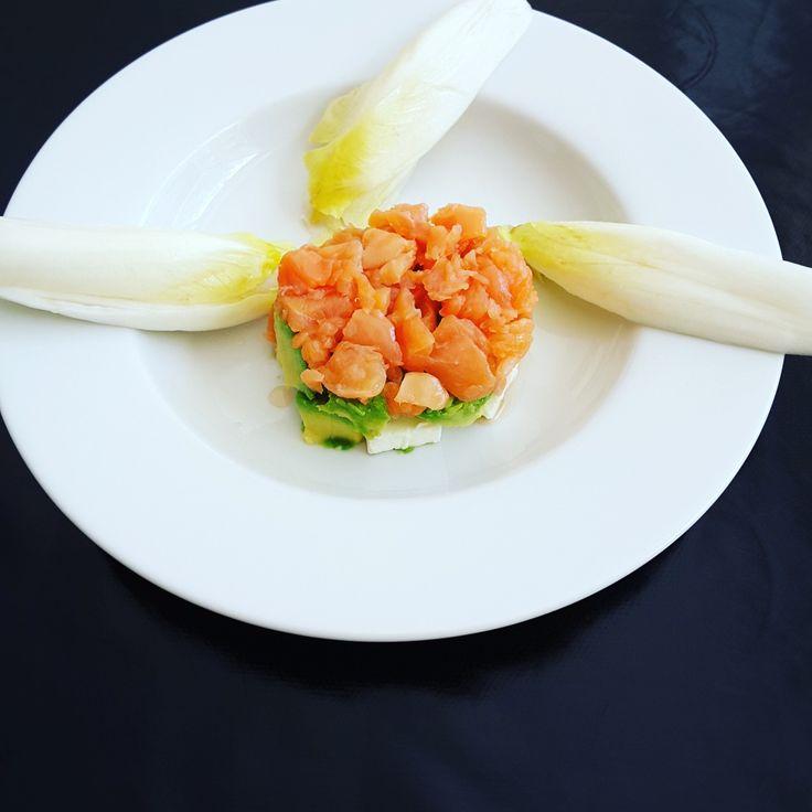 Tartare de saumon sur lit d'avocat et de fromage frais, accompagné d'endives