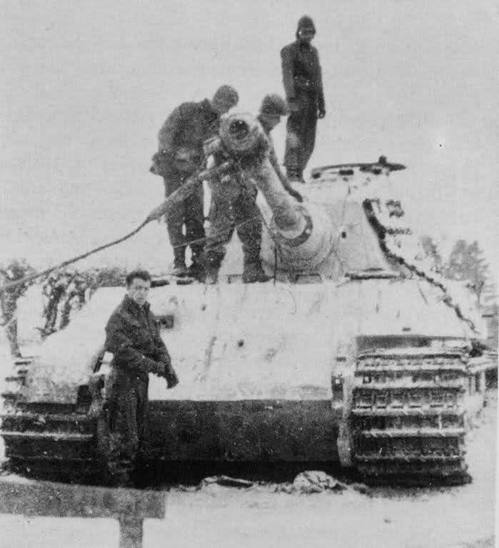 Two American soldiers inspect a destroyed German King Tiger tank, Belgium, 1944