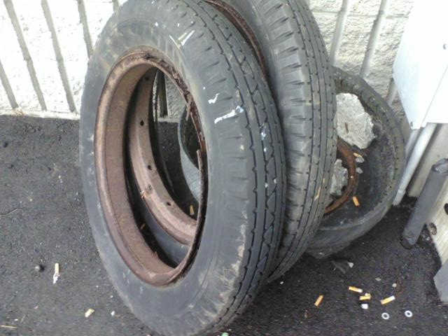 two old car wheels left to weather outside a tire shop