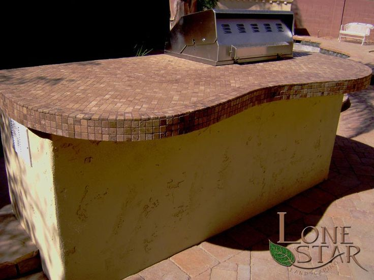 Barbecue With A Curved Countertop And Travertine Tile Trim