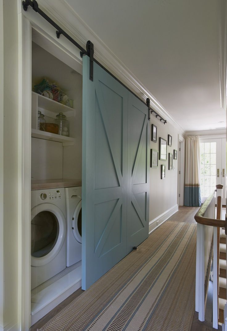 Second floor landing features concealed laundry room hidden behind blue barn door as well as brown and blue striped runner. Hall laundry room with open cubbies over white front-load washer and dryer next to wall of photos and French doors covered in two-tone curtains.