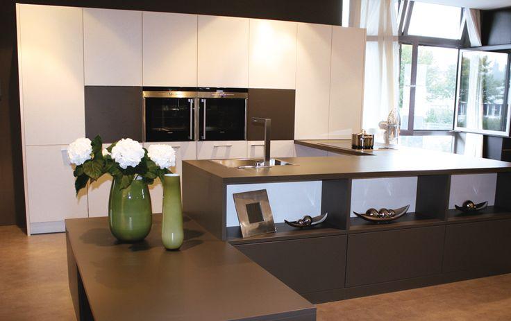 Moderne keuken met zwart kookeiland voorzien van een gootsteen. De keukenkast aan de muur heeft witte keukenkasten en verschillende ingebouwde keukentoestellen.