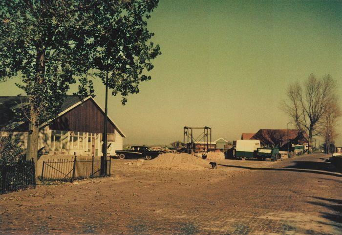 Haije Dijkstra begint in 1952 met zijn timmerbedrijf in een houten schuur aan het Westeinde.  Begin jaren zestig verhuist het bedrijf naar de Meerweg. Links op de voorgrond het hek van de boerderij van Hornstra met daarachter de pas gebouwde timmerwerkplaats en kantoor van aannemingsbedrijf Dijkstra. In het midden de overslag van de CBO en rechts op de achtergrond de woning van de Helling.