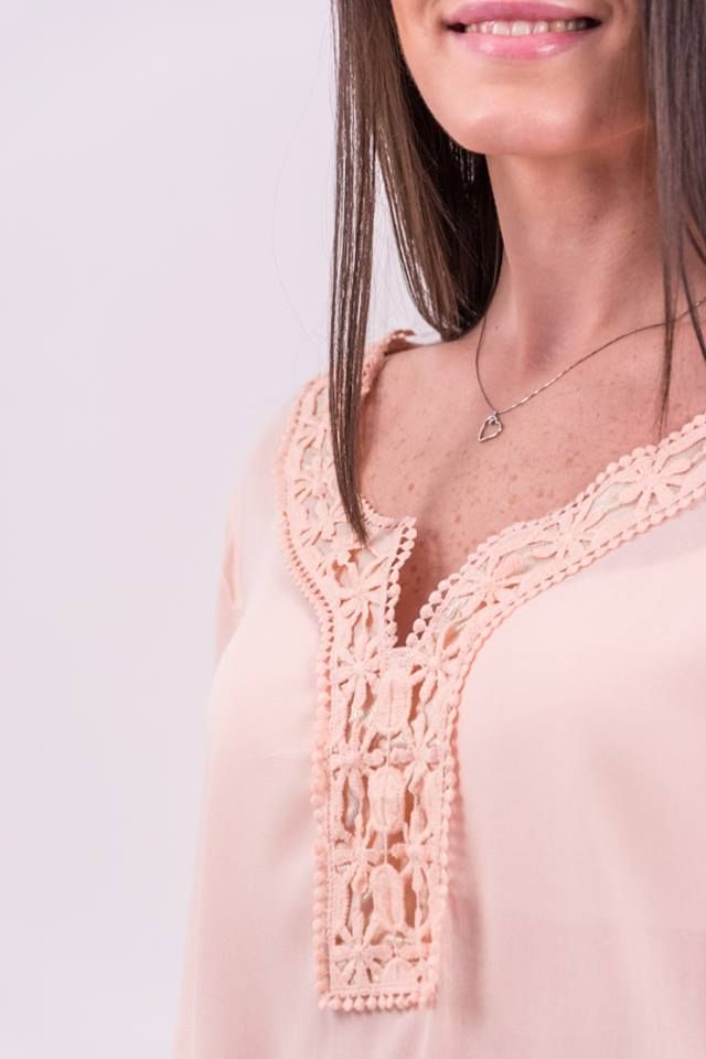 Bluză din material texturat fin, vaporos, de culoare roz somon cu decolteu în V. Este acccesorizată în partea frontală, in zona decolteului cu o broderie decorativă în aceeași nuanță. Mâneci lungi cu manșete accesorizate cu nasturi. Terminație asimetrică, în colțuri. Accesorii: baretă aplicată pe mânecă care se prinde cu nasture oferind posibilitatea de a plia mâneca și de a o purta 3/4.