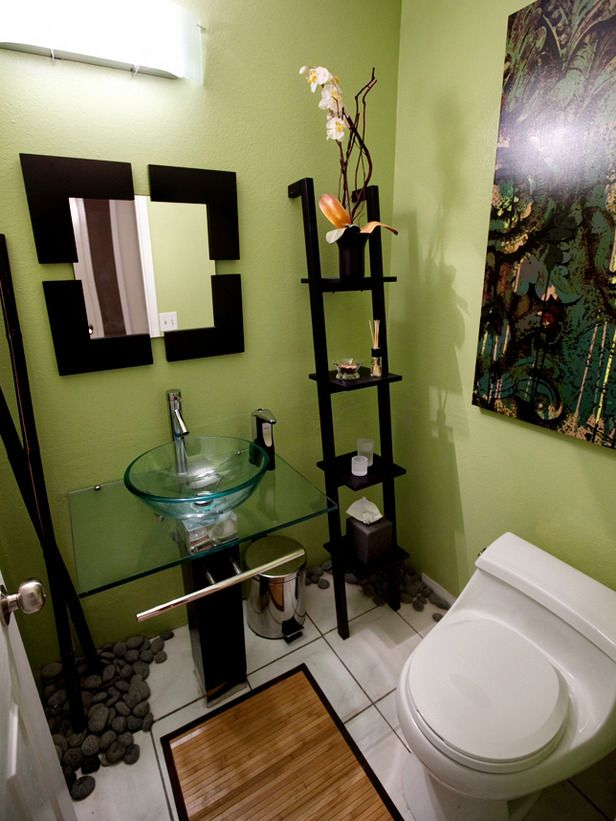 If you think a small bathroom limits design potential, take a look at this DIY space. Created in one weekend for about $1,000, it features a bold color palette and artwork, sleek finishes and stones on the floor.