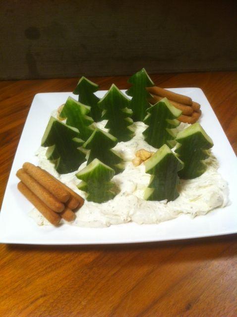 Kerstdiner hapje groep 5: Komkommer kerstbomen in roomkaas-sneeuwlandschap. Boomstammetjes van volkoren soepstengels en 'zwerfkeien' van hazelnoten.