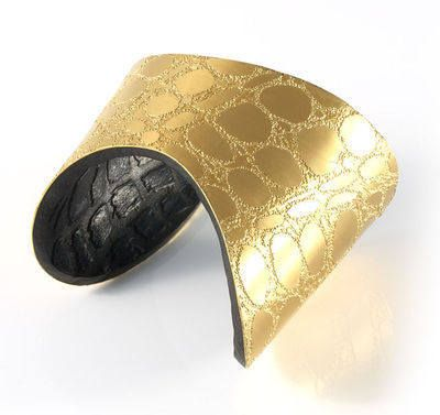 A distinctive gold plated metal cuff lined with embossed chocolate coloured leather.  The cuff has a highly textured finish which is achieved by transferring the texture onto the piece using manual etching and embossing techniques.  The cuff has a beautiful shape that sits perfectly on the wrist.