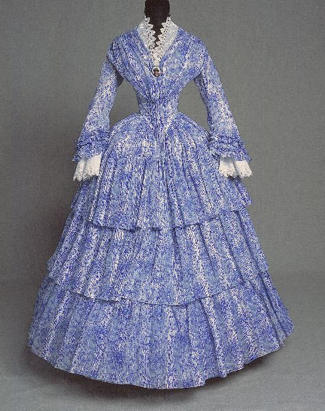 1850s gown  KM 44664   ::   klänningObjektbeskrivningTätmönstrad i klarblått på vit botten med rokokokartuscher och blomsterrankor, snibbliv, urringad hals och halvlång, vid ärm med volanger, tre volanger på kjolen.