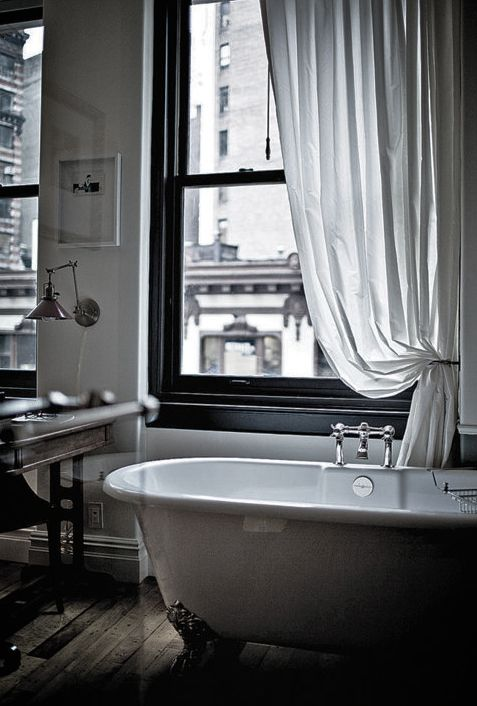 Quintessential effortless city living. Sheer white floor grazing window coverings, partially covering bustling city streets below from a classic white tub w/ gold claw feet. #simple  #bathtime #apartment #B