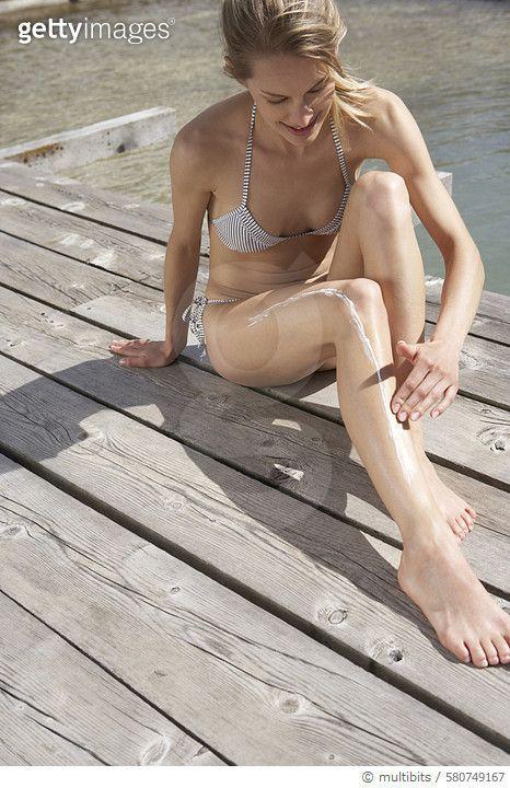 Woman sitting on planks putting on suncream - gettyimageskorea